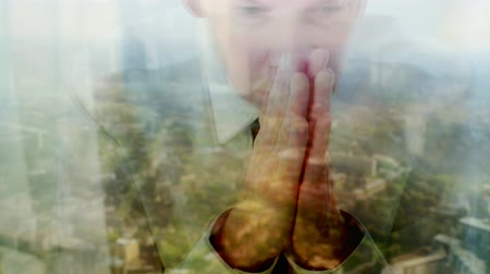 Reflection of a caucasian businessman praying against a window with a cityscape behind  themes of belief thankful spirituality religious Dostupné videozáznamy