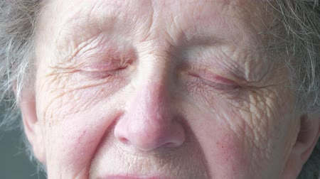 Close up portrait of a senior caucasian woman opening her eyes themes of retirement senior aging process portrait Dostupné videozáznamy