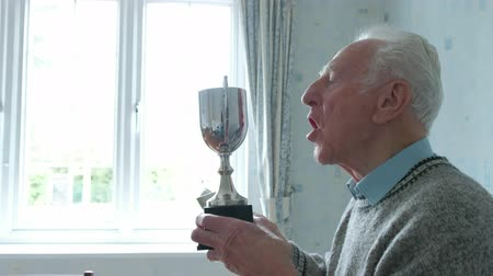 Senior caucasian man cleaning his trophy in his dining room themes of retirement sportsman winning pride Dostupné videozáznamy