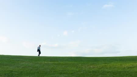 konuları : Low angle view of a Solitary middle aged Caucasian businessman walking over a hill