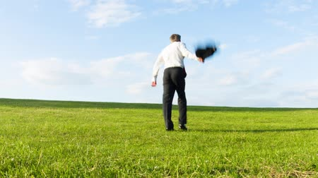 Carefree happy middle aged Caucasian businessman throwing off his jacket as he walks over a hill