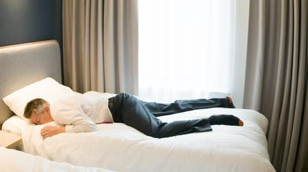 konuları : Caucasian business traveller climbing onto hotel bed exhausted