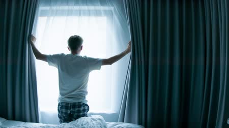 Middle aged Caucasian man opening curtains looking through window in a hotel room beginning of a new day