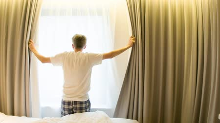 hátsó megvilágítású : Middle aged Caucasian man opening curtains looking through window in a hotel room beginning of a new day