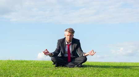 Businessman practicing yoga in the lotus position on the ridge of a hill in a park Dostupné videozáznamy