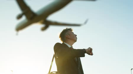 Low angle view of a successful Middle aged Caucasian businessman ready for departure checking his watch as a defocussed passenger plane flies overhead Dostupné videozáznamy