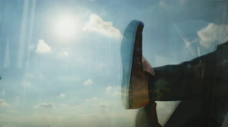 dangle : Reflection of a man kicking off his shoes backlit by the sun Stock Footage