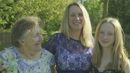 parentes : Portrait of a Caucasian Grandmother, her daughter and grand daughter looking at the camera in the garden Stock Footage