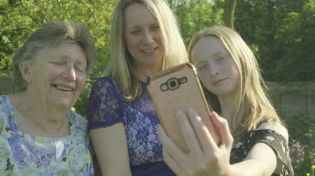 photography themes : Grandmother, her daughter and grand daughter taking a selfie on a smartphone in the garden Stock Footage