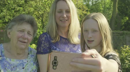 país : Grandmother, her daughter and grand daughter taking a selfie on a smartphone in the garden Vídeos