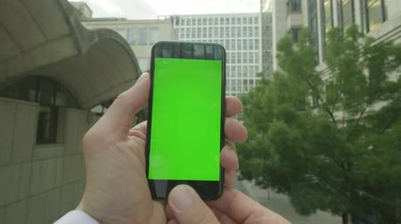 přenosný : Personal perspective of a Caucasian man relaxing using a Green-screen Chroma-key smartphone outside the office