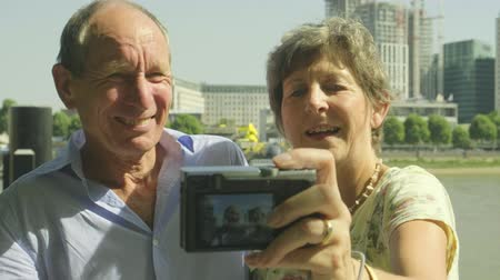 covent : Active senior caucasian tourist couple kissing taking a selfie on a digital camera in london with the river thames behind