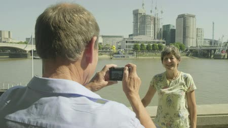 photography themes : Active senior woman posing for her husband while on vacation with the river thames behind in london