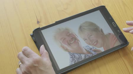 photography themes : Senior caucasian woman looking at old photos of herself on a tablet computer Stock Footage
