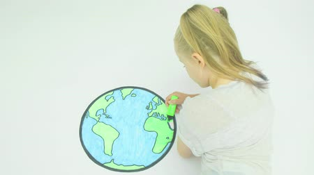 metaphors : Pre teen caucasian girl colouring in a map of the world