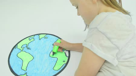 ambientalmente : Pre teen caucasian girl colouring in a map of the world