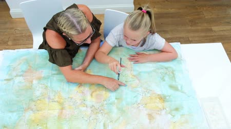szándékozik : Mother and daughter looking at a map of the world