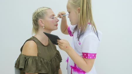 imitação : Pre teen caucasian girl putting make up onto her mothers face Stock Footage