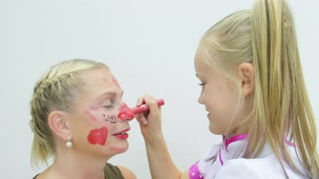 womanhood : Pre teen caucasian girl putting make up onto her mothers face Stock Footage