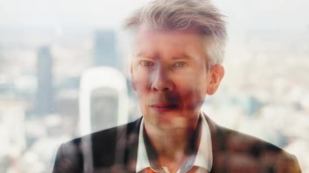 drudgery : Reflection of a daydreaming businessman in contemplation looking out of a window London skyline behind Stock Footage