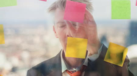 task : Reflection of a creative businessman brainstorming ideas putting post it notes on to a window London skyline behind