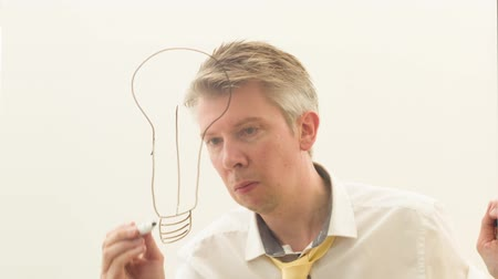 deha : Reflection of a creative businessman brainstorming drawing a lightbulb onto glass