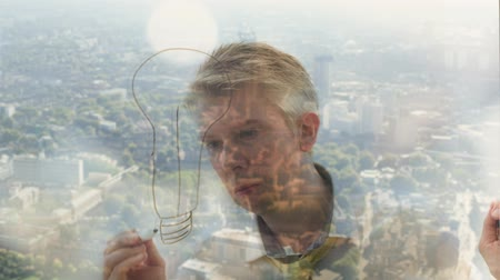 kreslit : Reflection of a creative businessman brainstorming drawing a lightbulb onto glass