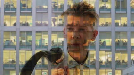 drudgery : Reflection of a businessman looking out of a window then leaving the office
