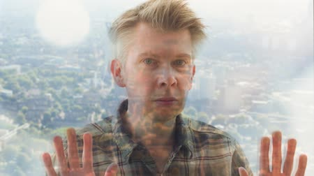 on camera : Reflection of a Caucasian man daydreaming looking out of a window Stock Footage