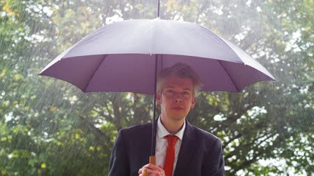 torrential : Caucasian businessman sheltering underneath an umbrella in the torrential rain