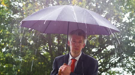 předpovídání : Caucasian businessman sheltering underneath an umbrella in the torrential rain