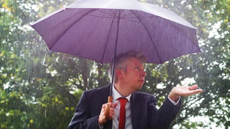 vulnerability : Caucasian businessman sheltering underneath an umbrella in the torrential rain