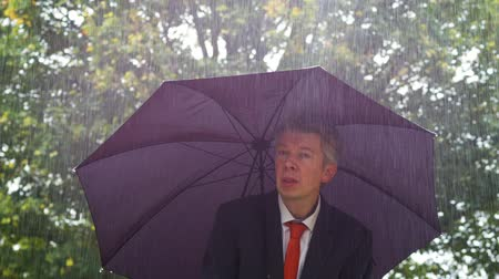 torrential rain : Caucasian businessman sheltering underneath an umbrella in the torrential rain