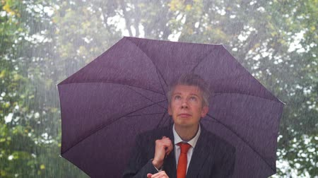 metaphors : Caucasian businessman sheltering underneath an umbrella in the torrential rain