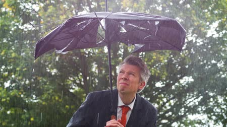 torrential rain : Caucasian businessman sheltering underneath a broken umbrella in the rain