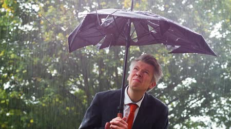 adversidade : Caucasian businessman sheltering underneath a broken umbrella in the rain
