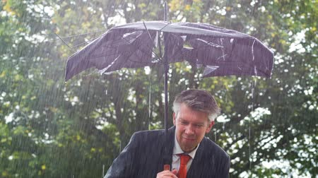 porażka : Caucasian businessman sheltering underneath a broken umbrella in the rain