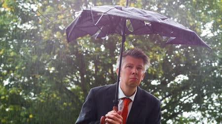 metaphors : Caucasian businessman sheltering underneath a broken umbrella in the rain