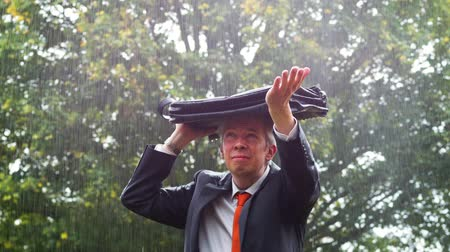 porażka : Rear view of a drenched caucasian businessman sheltering underneath his bag in the rain Wideo