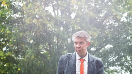 předpovídání : Drenched caucasian businessman caught out in the rain without an umbrella