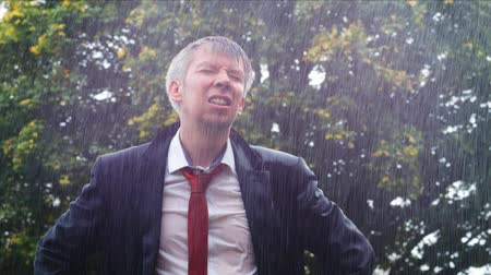 adversidade : Drenched caucasian businessman caught out in the rain without an umbrella