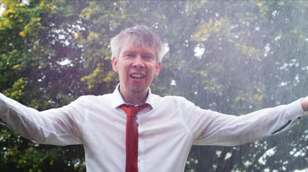 porażka : Drenched caucasian businessman caught out in the rain without an umbrella