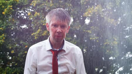 vulnerability : Drenched caucasian businessman caught out in the rain without an umbrella