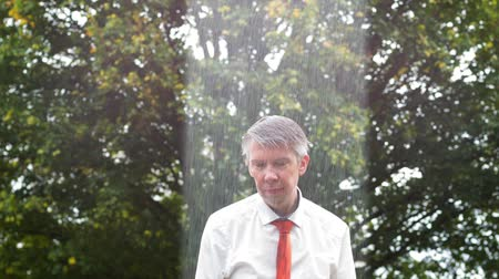 unlucky : Localised rain shower over a drenched caucasian businessman caught out in the rain without an umbrella