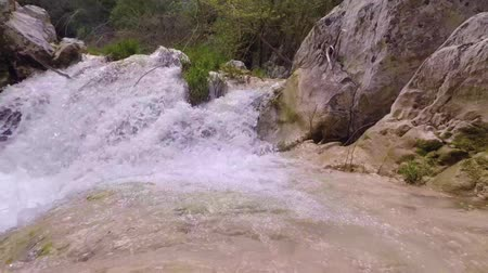 tarde : Slow motion handheld shot of a small waterfall in Polilimnio - Greece