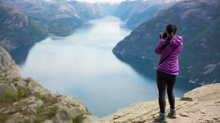 norvégia : Nature photographer tourist with camera shoots while standing on top of the mountain. Beautiful Nature Norway Preikestolen or Prekestolen.