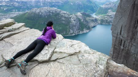 pulpit rock : Woman looking at the landscape from a height. Beautiful Nature Norway Preikestolen or Prekestolen. Stock Footage