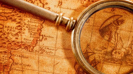 história : Vintage still life. Vintage magnifying glass lies on an ancient world map in 1565