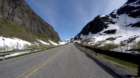 Driving a Car on a Mountain road in Norway with high snow wall