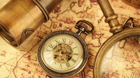 tesouro : Vintage magnifying glass, compass, telescope and a pocket watch lying on ancient world map in 1565. Stock Footage